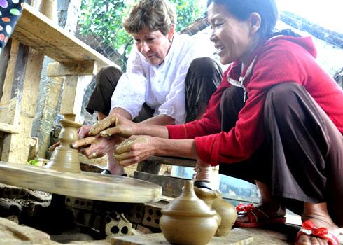 """Nghệ nhân làng gốm hướng dẫn du khách làm sản phẩm gốm thủ công bằng bàn xoay. Bà Swartz Nita(người Mỹ) chia sẻ: """"Lần đầu tiên đến Việt Nam, ở lại phố cổ Hội An 3 ngày nhưng chúng tôi đã có nhiều trải nghiệm thú vị khi về thăm cuộc sống bình dị của người dân bản địa. Thích nhất là được người dân chỉ cách làm gốm thủ công giữa làng gốm cổ Thanh Bình. Trong năm tới, vợ chồng tôi sẽ đưa con, cháu tiếp tục về nơi đây""""."""